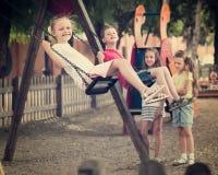 Filles et garçons balançant sur le terrain de jeu Images stock
