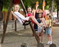 Filles et garçons balançant sur le terrain de jeu Photographie stock