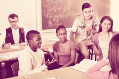 Filles et garçons détendant ensemble entre les classes Photo libre de droits