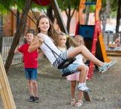 Filles et garçons de sourire balançant sur le terrain de jeu Photos libres de droits