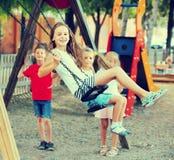 Filles et garçons de sourire balançant sur le terrain de jeu Photos stock