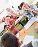 Filles et garçons soulevant leurs mains dans la classe Photographie stock
