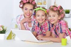 Filles et mère dans des bigoudis de cheveux avec l'ordinateur portable image libre de droits