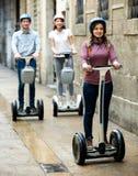 Filles et type voyageant par la ville par des segways Photo stock
