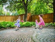Filles et un garçon jouant dehors à une partie de Pâques image stock