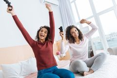 Filles extrêmement heureuses célébrant la victoire après avoir joué des jeux vidéo Photos libres de droits