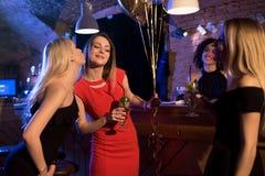 Filles félicitant leur ami avec son anniversaire tout en célébrant l'événement à la boîte de nuit Photo stock