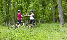 Filles faisant du vélo dans la forêt Photos stock