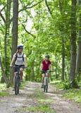 Filles faisant du vélo dans la forêt Photo stock