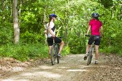 Filles faisant du vélo dans la forêt image libre de droits