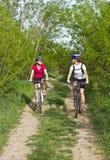 Filles faisant du vélo dans la forêt Images libres de droits