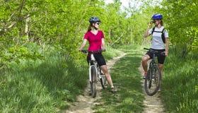 Filles faisant du vélo sur un chemin forestier photo stock