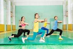 Filles faisant le long pas en avant dans la salle de gymnastique Photographie stock libre de droits