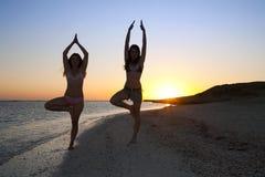 Filles faisant le yoga contre le coucher du soleil Photos stock