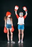 Filles folâtres dans des gants de boxe d'isolement sur le noir Photo stock