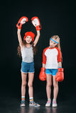 Filles folâtres dans des gants de boxe d'isolement sur le noir Photographie stock libre de droits
