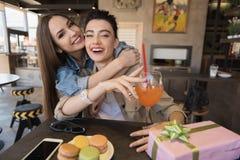 Filles gaies étreignant dans un café Photos stock