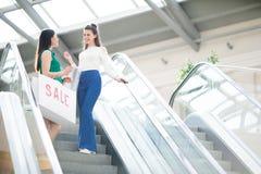 Filles gaies abaissant l'escalator dans le mail Images stock