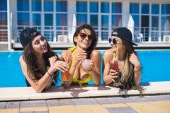Filles gaies buvant des cocktails dans la piscine Photo stock