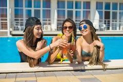 Filles gaies buvant des cocktails dans la piscine Images stock