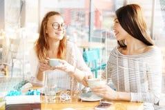 Filles gaies buvant du café ensemble Image stock