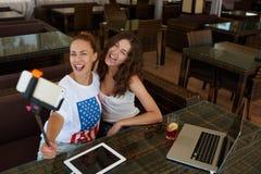 Filles gaies de hippie posant tout en se photographiant pour la photo sociale de réseau pendant la pause de midi en café, Photographie stock libre de droits