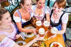 Filles grillant avec de la bière de blé dans le bar bavarois Photos stock