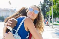 Filles heureuses étreignant tout en marchant dans la ville Image libre de droits