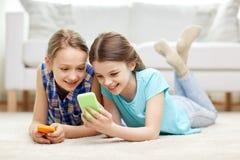 Filles heureuses avec des smartphones se trouvant sur le plancher Photos libres de droits