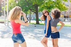 Filles heureuses avec l'appareil-photo dehors dans la ville Photos stock