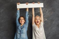 Filles heureuses avec la bannière blanche vide au fond foncé de studio Images stock