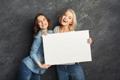 Filles heureuses avec la bannière blanche vide au fond foncé de studio Photographie stock libre de droits