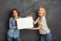 Filles heureuses avec la bannière blanche vide au fond foncé de studio Photographie stock