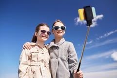 Filles heureuses avec le bâton de selfie de smartphone Photographie stock