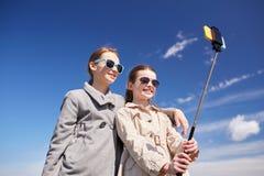 Filles heureuses avec le bâton de selfie de smartphone Image libre de droits