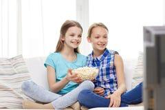Filles heureuses avec le maïs éclaté regardant la TV à la maison Photo stock