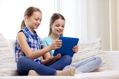 Filles heureuses avec le PC de comprimé se reposant sur le sofa à la maison Image stock