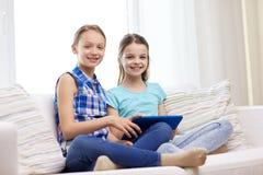 Filles heureuses avec le PC de comprimé se reposant sur le sofa à la maison Photos stock