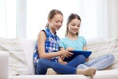 Filles heureuses avec le PC de comprimé se reposant sur le sofa à la maison Photo stock