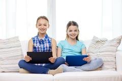 Filles heureuses avec le PC de comprimé se reposant sur le sofa à la maison Photographie stock