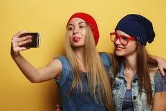 Filles heureuses avec le smartphone au-dessus du fond jaune Individu heureux Photographie stock