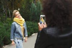 Filles heureuses avec le smartphone dehors en parc Photos stock