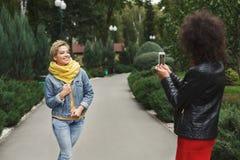 Filles heureuses avec le smartphone dehors en parc Photo stock