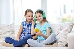 Filles heureuses avec le smartphone et les écouteurs Photographie stock