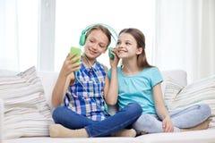 Filles heureuses avec le smartphone et les écouteurs Photos libres de droits