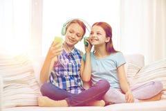 Filles heureuses avec le smartphone et les écouteurs Images libres de droits
