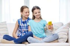 Filles heureuses avec le smartphone prenant le selfie à la maison Image stock