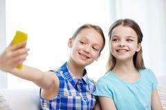 Filles heureuses avec le smartphone prenant le selfie à la maison Photo stock