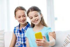Filles heureuses avec le smartphone prenant le selfie à la maison Photographie stock libre de droits