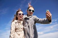 Filles heureuses avec le smartphone prenant le selfie dehors Photos stock